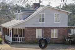 Tire swing hanging next to typical southern house in Georgia, focus on Tire swing