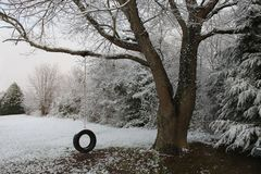 Tire swing in a late snow Stock Photo