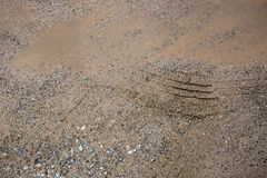 Tire trace on the gravel beside water in the pothole on the rained day. Royalty Free Stock Photos