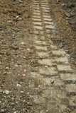 Tire track in a dirt road Stock Images