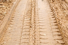 Tire track on muddy road Stock Photos