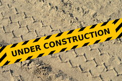 Tire track in a sand with under construction yellow tape Royalty Free Stock Images