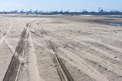 Tire tracks on the beach and Rotterdam industry in background Royalty Free Stock Photos