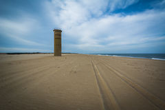 Tire tracks on the beach and a World War II Observation Tower at. Cape Henlopen State Park in Rehoboth Beach, Delaware stock image