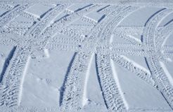 Tire tracks crossing the snowy terrain. Vehicle tracks crossing the snowy winter terrain in different directions royalty free stock image