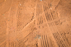 Tire tracks on dirt ground. Tire tracks on brown dirt ground Royalty Free Stock Photo