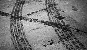Tire tracks and footstep on the asphalt Royalty Free Stock Photos
