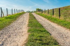 Tire tracks on a ramp to the top of a Dutch. Tire tracks on a sandy driveway to the top of a Dutch dike. Beside the road are fences on both sides made of wooden royalty free stock photography