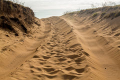 Tire tracks in sand dunes over hill Royalty Free Stock Image