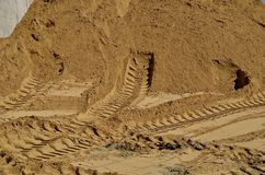 Tire tracks in the sand. Tire tracks of heavy equipment are evident on the sand of a huge pile to be used in a construction site stock photos