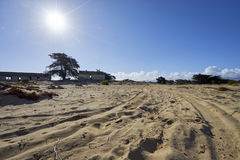 Tire tracks through the sand leading to deserted military base. View from the dunes in Monterey County, California towards abandoned portion of Fort Ord stock image