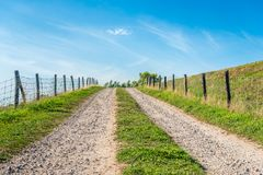 Tire tracks on a ramp to the top of a Dutch. Tire tracks on a sandy driveway to the top of a Dutch dike. Beside the road, man-made fences are made of wooden royalty free stock photos