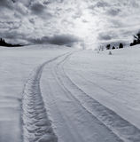 Tire tracks in snow off into distance Stock Images