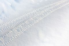 Tire tracks on a snowy road. Winter road not cleared of snow. Hard to drive. Village country road.  stock photo