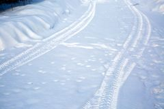 Tire tracks on a snowy road. Winter road not cleared of snow. Hard to drive. Village country road.  royalty free stock image