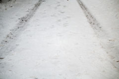 Tire tracks in winter on a road. The tracks of a car on a snow covered road Royalty Free Stock Photos