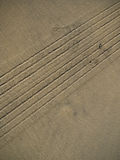 Tire treads track in sand. Wet beach sand with car tire tracks in it Stock Photography