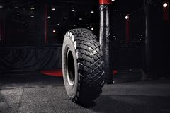 Tire wheel for occupation workout gym, dark background.  stock photos