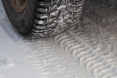 Tire for winter with spikes and its imprint on the road. Covered with snow royalty free stock photo