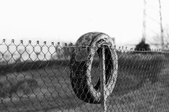 Tire on the wire mesh fence Royalty Free Stock Image