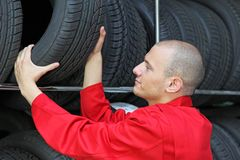 Tire workshop. A motivated worker in a tire workshop is checking the stock Royalty Free Stock Photos