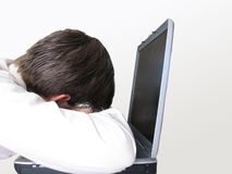 Tired. Someone leans on his laptop to get some rest after some hard work on it stock photos