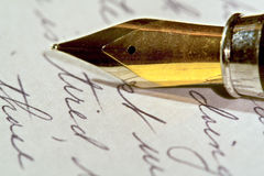 Tired. A golden pen-nib with handwritten words Royalty Free Stock Photography