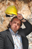 Tired. Man with helmet on workplace Royalty Free Stock Photo
