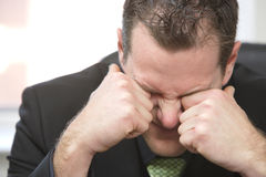 Tired. A tired business man rubs his eyes Stock Photography