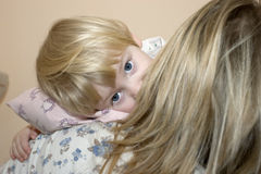 Tired. Young tired girl with head on the shoulder of her mother Royalty Free Stock Photography