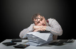 Tired accountant. Humorous portrait a tired accountant sleeping on his workplace royalty free stock photos