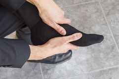 Tired and aching feet. Businessman massages tired feet and aching Stock Photo