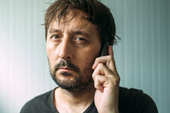 Tired adult man talking on mobile phone Royalty Free Stock Image