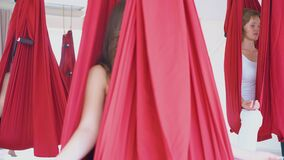 Women relax in red hammocks with fingers in mudra position