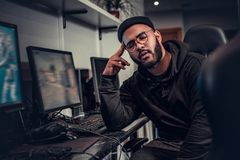 Tired African American bearded gamer wearing hoodie and cap fell asleep sitting at the computer table in a gaming club royalty free stock images