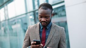 Tired African American businessman reads something in his smartphone standing outside. Man sms texting using app on