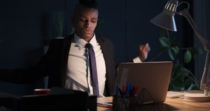 Businessman stretching while working late night in office stock video footage