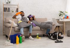 Tired african-american couple is wiping foreheads after housecleaning. Housekeeping is exhausting. Tired young african-american couple is wiping foreheads while royalty free stock image