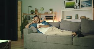 Tired african american man watching tv at night yawning lying on couch alone. Tired african american man is watching tv at night yawning lying on couch alone stock video
