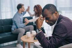 Tired african american psychiatrist in office with quarreling. Couple behind Stock Image