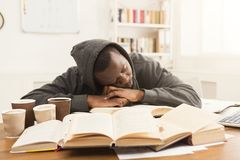 Black male student studying at table full of books. Tired african-american student sleeping on working table. Exhausted male student preparing for exams Royalty Free Stock Photos