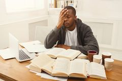 Black male student studying at table full of books. Tired african-american student studying at working table. Exhausted male student preparing for exams Royalty Free Stock Photos