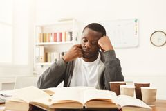 Black male student studying at table full of books. Tired african-american student studying at working table. Exhausted male student preparing for exams Stock Photos