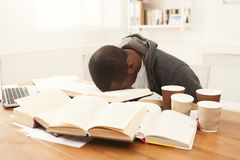 Black male student studying at table full of books. Tired african-american student studying at working table. Exhausted male student preparing for exams Royalty Free Stock Images