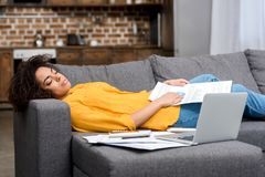 tired african american woman sleeping on couch after work Stock Photos