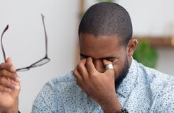 Tired african businessman taking off glasses rubbing dry irritated eyes royalty free stock photos