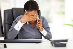Tired african businesswoman. Tired african american businesswoman using landline phone Royalty Free Stock Photo