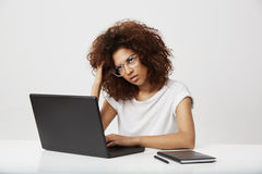 Tired african businesswoman thinking working at laptop over white background. Copy space Royalty Free Stock Photos