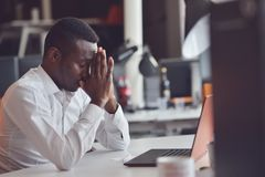 Tired African man sitting at a office after a hard workday, working on laptop, trying to concentrate. Tired African man sitting at a cafe after a hard workday Royalty Free Stock Images