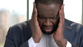 Tired african office worker suffering from headache. Stressed black man in suit feeling headache and massaging head to relax and reduce pain indoor, close up stock video footage